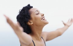 Happy and healthy African American woman relaxing with open arms outdoors